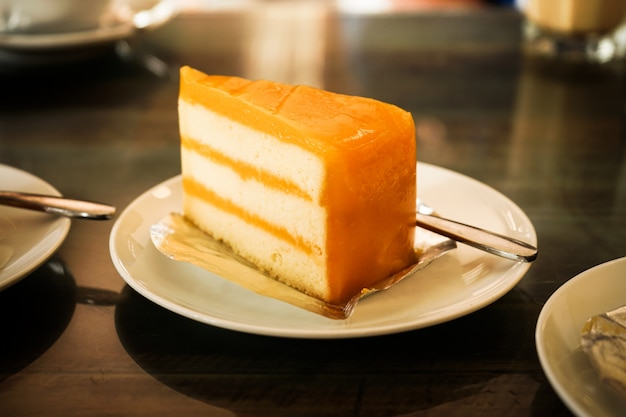 Fruit orange cake on white plate dressert eat with coffee relax time in resturant