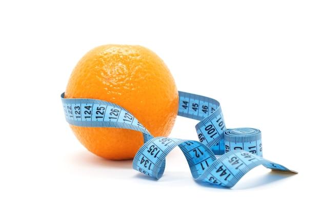 과일 오렌지는 흰색 바탕에 파란색 측정 테이프로 싸여 있습니다 프리미엄 사진