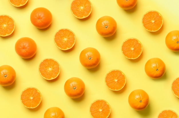 Fruit pattern of fresh orange slices on yellow background. pop art design, creative summer concept. half of citrus in minimal flat lay style.