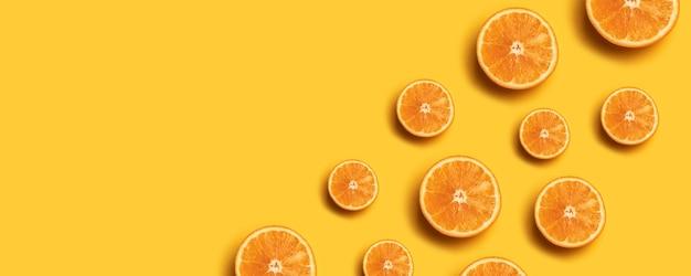 Fruit pattern of fresh orange slices on yellow background.