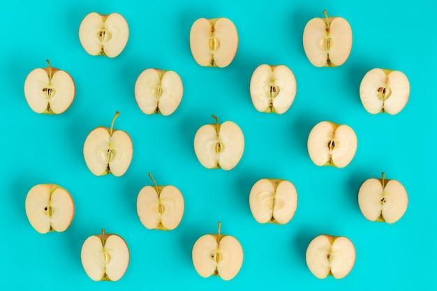 Фруктовый образец половинок яблока на синем фоне. плоская планировка, вид сверху. продовольственный фон.