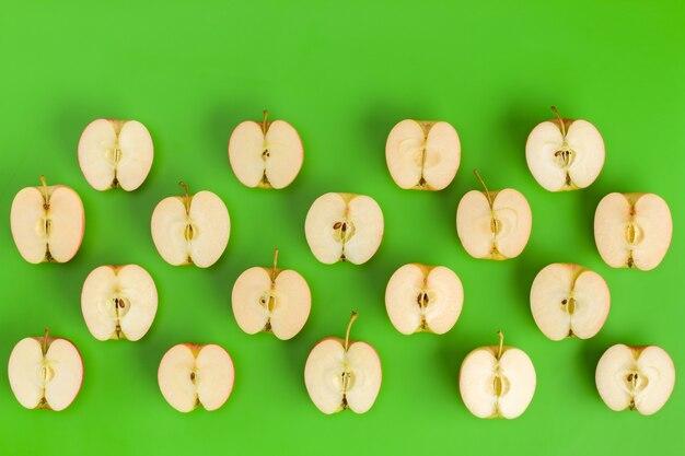 Фруктовый образец половинок яблока на зеленом фоне. плоская планировка, вид сверху. продовольственный фон.