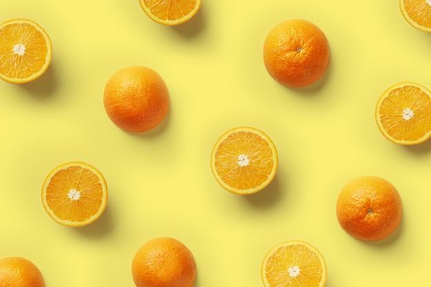 黄色の背景に新鮮なオレンジスライスのフルーツパターン。上面図。スペースをコピーします。ポップアートのデザイン、創造的な夏のコンセプト。最小限のフラットレイスタイルの柑橘類の半分。バナー