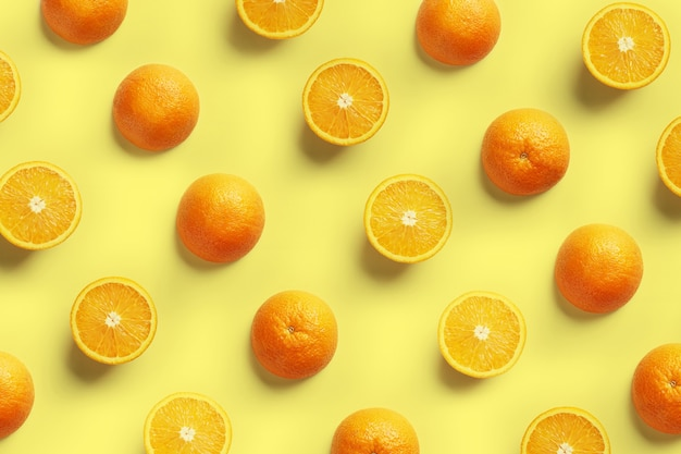 黄色の背景に新鮮なオレンジスライスのフルーツパターン。上面図。スペースをコピーします。