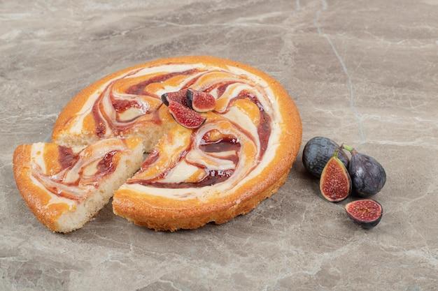 Torta di frutta e fichi freschi su spazio marmoreo.