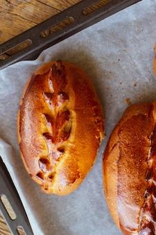 オーブンからのフルーツパイベーキングデーチェリーと甘いペストリー伝統的なロシアのペストリーベリーとロシアのパンチェリーとピロシキオーブンからの焼き菓子のクローズアップパイフードデー