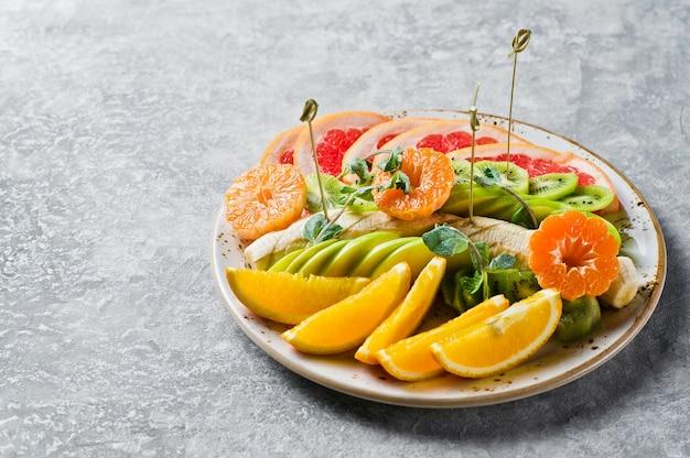 Fruit plate, grapefruit, tangerine, kiwi, orange, banana, apple.