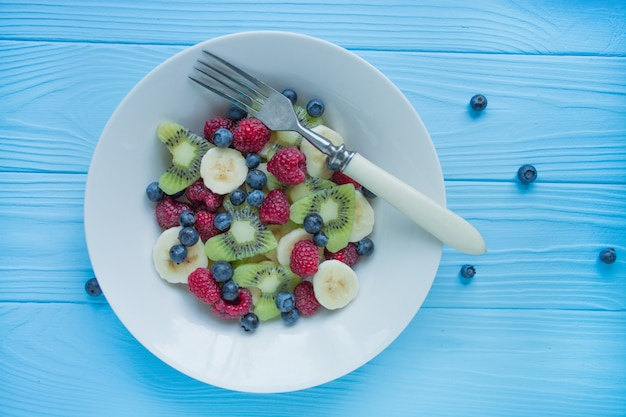 Fruit plate. kiwi, banana, blueberry and raspberry fruit salad. wood .
