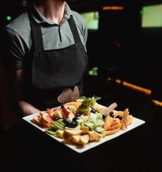 Тарелка с фруктами на руке официанта