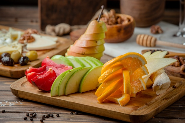 Fruit plate with apple, banana, prune and orange slices