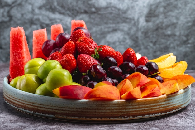 Fruit plate with watermelon greengage plum grape peach apricot strawberry melon and cherry