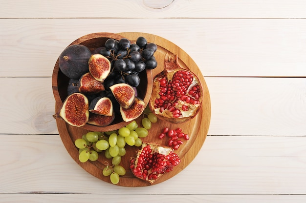 Fruit platter  with figs, grapes, pomegranate on wooden surface