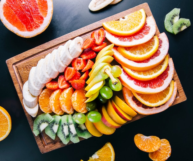 Fruit platter with mixed sliced fruits.
