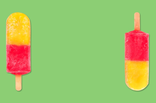 Fruit popsicle  ice cream stick on green background  pineapple and strawberry popsicle called mini skirt at brazil pastel color  copy space