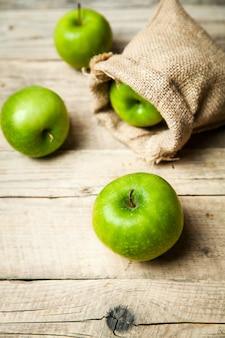 フルーツ。黄麻布、木製のテーブルの上に熟した青リンゴ