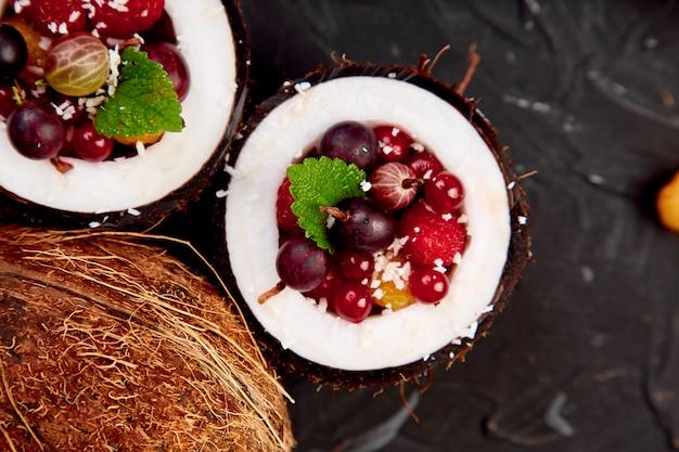 Fruit salad agrus, gooseberry, rasbberry in coconut shell bowl