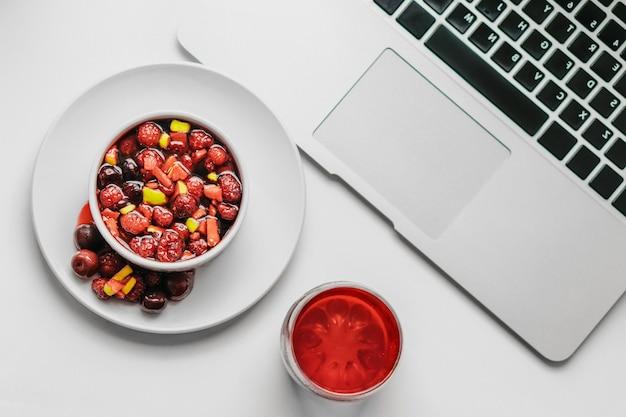 Фруктовый салат и сок с ноутбуком на белом. концепция здорового завтрака.