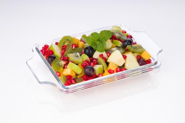 Фруктовый салат в прозрачной стеклянной таре с белым фоном.