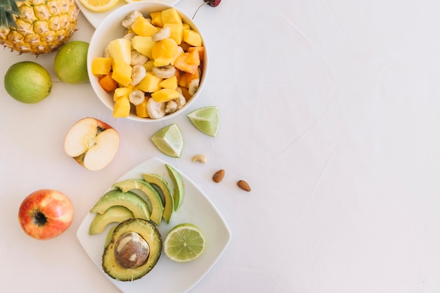 Fruit salad and avocado slices on white background