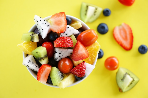 Fruit salad bowl fresh summer fruits and vegetables healthy organic food strawberries orange kiwi blueberries dragon fruit tropical grape pineapple tomato lemon on yellow