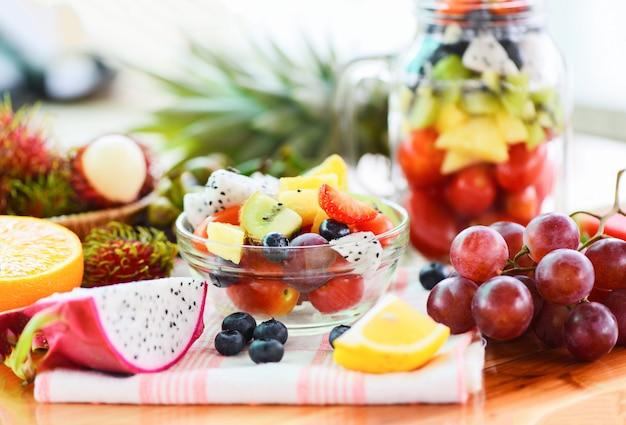Fruit salad bowl fresh summer fruits and vegetables healthy organic food strawberries orange kiwi blueberries dragon fruit tropical grape tomato lemon rambutan pineapple