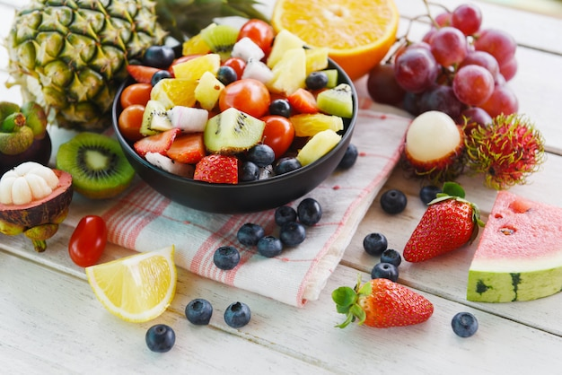 Fruit salad bowl fresh summer fruits and vegetables healthy organic food watermelon strawberries orange kiwi blueberries dragon fruit tropical grape tomato lemon rambutan pineapple