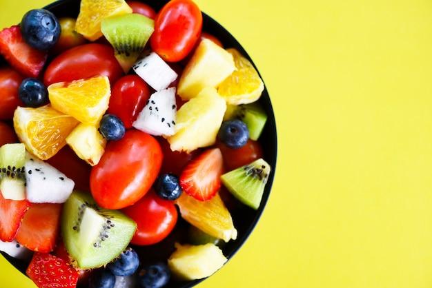 Fruit salad bowl fresh summer fruits and vegetables healthy organic food.