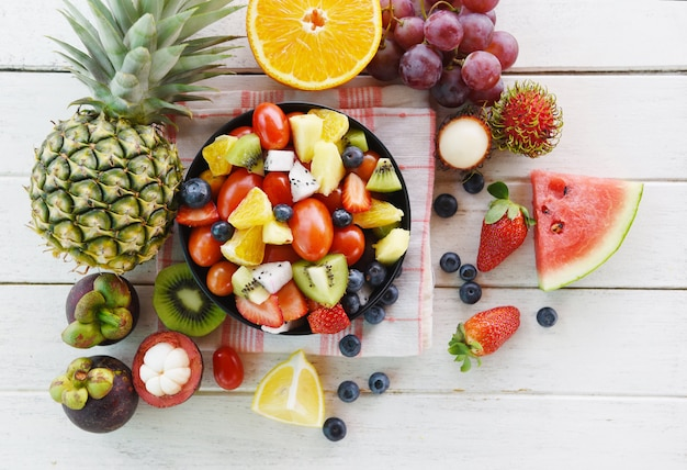 Fruit salad bowl fresh summer fruits and vegetables healthy strawberries orange kiwi blueberries dragon fruit tropical grape tomato lemon rambutan mangosteen pineapple watermelon
