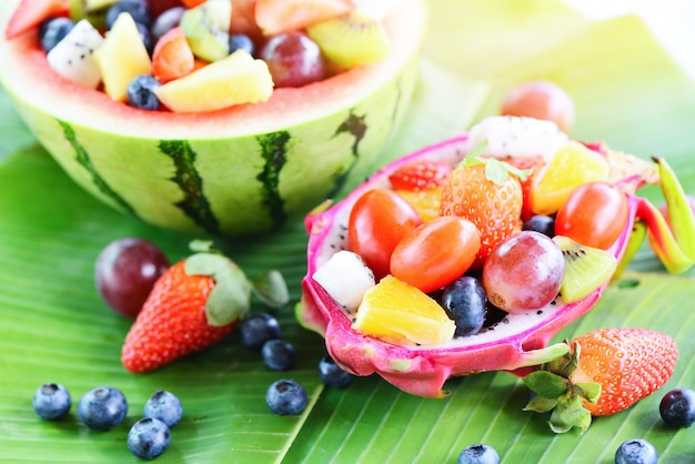 Fruit salad bowl served in a dragon fruit and watermelon vegetables healthy food strawberries orange kiwi blueberries grape pineapple tomato lemon fresh fruits tropical on banana leaf