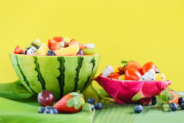 Fruit salad bowl served in dragon fruit and watermelon vegetables healthy food strawberries orange kiwi blueberries grape pineapple tomato lemon fresh summer fruits tropical on banana leaf