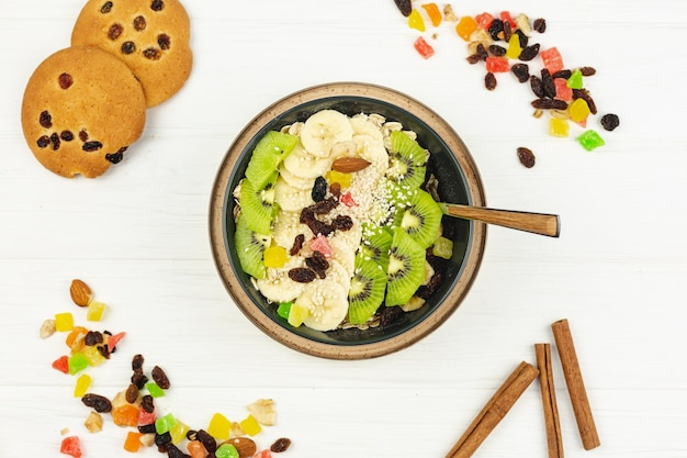 Fruit salad bowl with cookies and dry fruits on a white background
