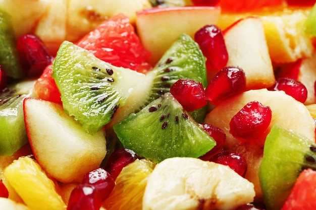 Fruit salad close-up in full screen, as a background. slices of fresh and healthy fruits