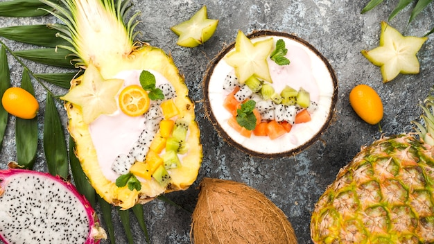 Fruit salad in coconut and pineapple plates top view