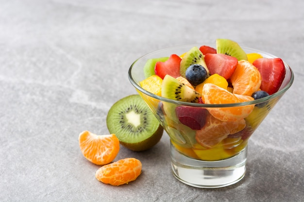 Fruit salad in crystal bowl on gray with copy space