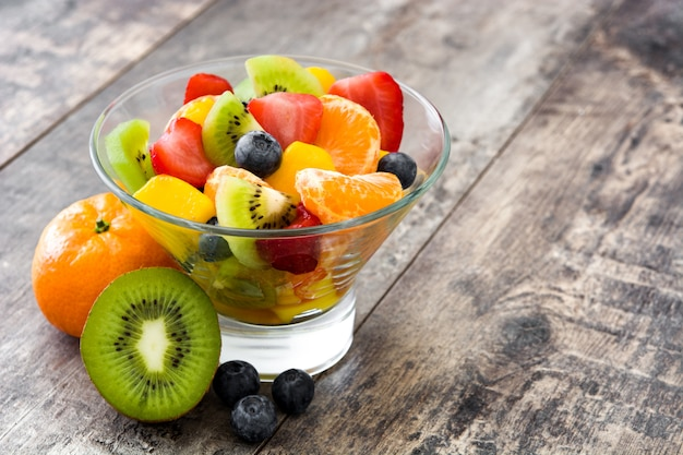 Fruit salad in crystal bowl on wooden table with copy space
