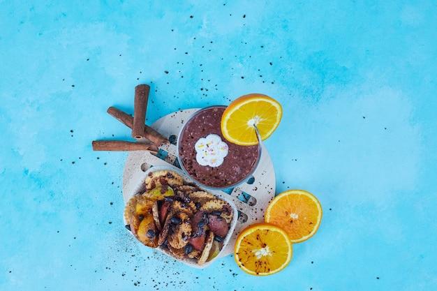 Macedonia di frutta e una tazza di cioccolata calda su blu, vista dall'alto.