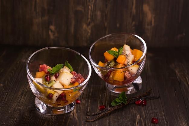 Fruit salad in glass bowls over dark background