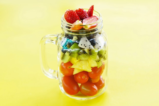 Fruit salad in a glass jar fresh summer fruits and vegetables healthy organic food strawberries kiwi blueberries dragon fruit tropical tomato pineapple on yellow