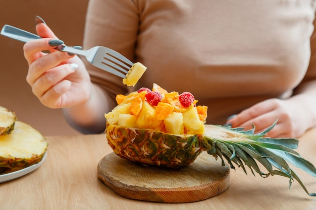 Fruit salad in half pineapple bowl. tasty tropical fruits salad eat woman in cafe. food fruit mix dessert served on cutting board in pineapple. high quality stock photo.
