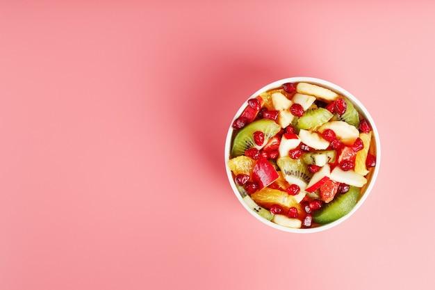 ピンクの背景にカップのフルーツサラダ。テキスト用の空き容量。健康的な食事のための新鮮でジューシーで健康的な果物のスライス。