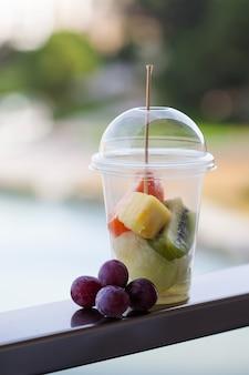Фруктовый салат в пластиковом стакане рядом с веткой винограда