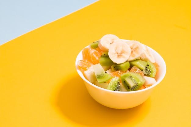 Фруктовый салат в небольшой белой миске на желтом фоне