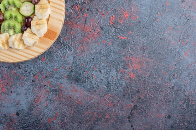 青い背景の上の木製の大皿にフルーツサラダ。