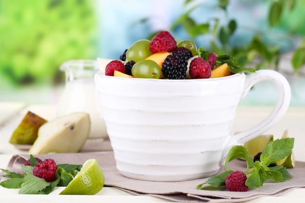 自然の表面の木製テーブルの上のカップのフルーツサラダ