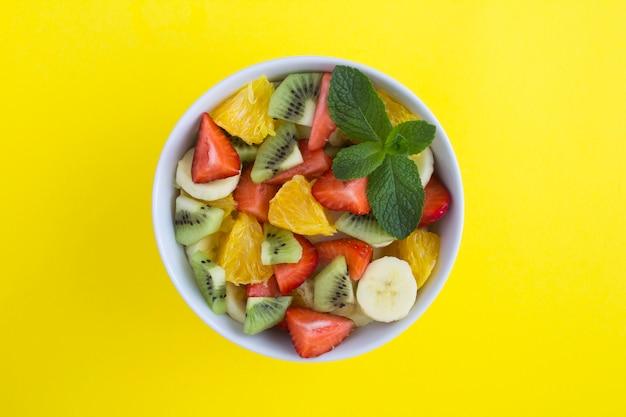 黄色の背景の中央にある白いボウルのフルーツサラダ。上面図。コピースペース。