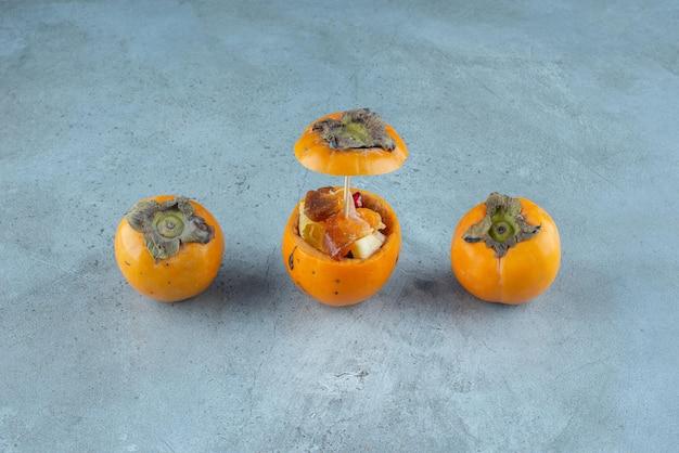 새겨진 노란색 대추 자두 안에 과일 샐러드.