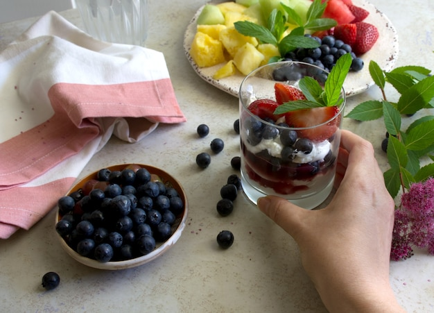 Fruit salad and natural greek yogurt with fresh berries hand holding glass with yogurt and fruits