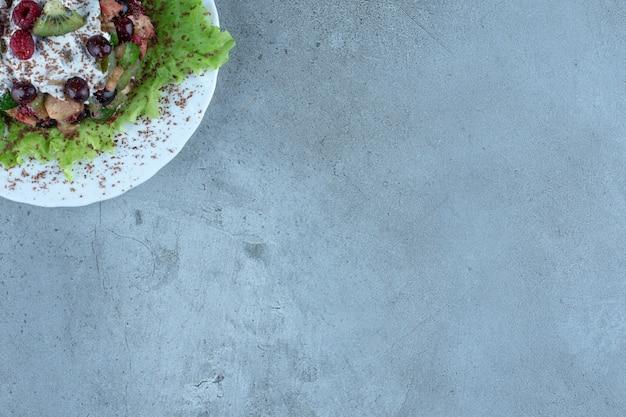 Фруктовый салат, заправленный сумахом, на мраморе.