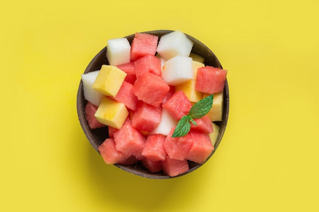 Fruit salad of watermelon, melon and mango in coconut bowl on yellow background. view from above.