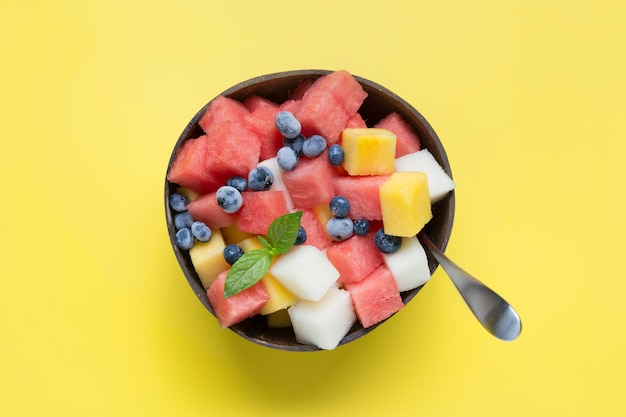 Fruit salad of watermelon, melon and mango in coconut bowl on yellow
